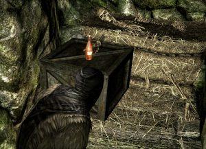 """Screenshot aus """"Skyrim"""": Ein Skelett liegt auf einem Heuballen und streckt seine Hand nach einer Flasche aus."""